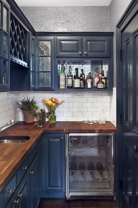 teal cabinets with rich-stained butcher block countertops and a white subway tile backsplash looks very bold