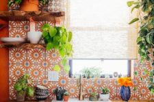 02 a bold orange kitchen with a bold printed tile backsplash and a wooden countertop looks super bright