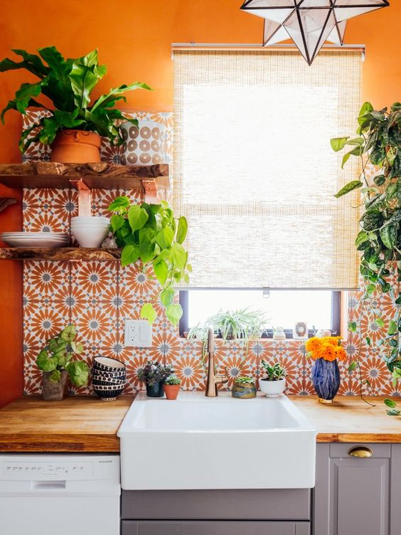 a bold orange kitchen with a bold printed tile backsplash and a wooden countertop looks super bright