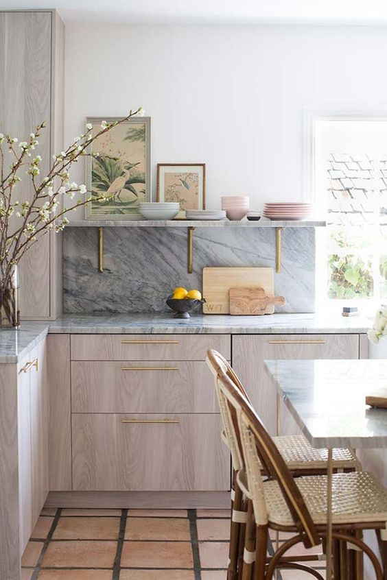 a chic contemporary kitchen with neutral cabinets, a grey kitchen backsplash and countertops and touches of gold for more chic