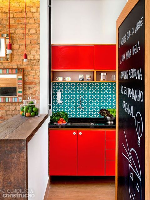 a bright red kitchen with black countertops and a bold turquoise tile backsplash looks like a super bold splash of color