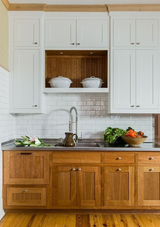 a cozy rustic space with rich-colored wooden cabinets and white ones plus a subway tile backsplash