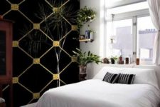 03 a small yet cute bedroom with a black and gold statement wallpaper wall that adds a calming moody touch to the space