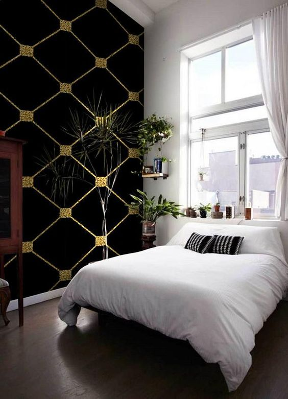 a small yet cute bedroom with a black and gold statement wallpaper wall that adds a calming moody touch to the space