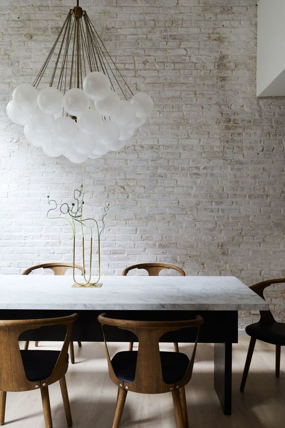 a whitewashed brick wall brings a rough touch to this refined space giving it a character this way