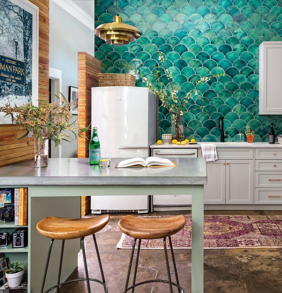 a chic contemporary kitchen with green fish scale tiles that cover the whole wall and give the space a pattern and color