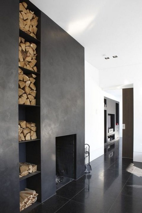 a dark concrete clad fireplace with open firewood storage built-in for a Nordic or minimalist space