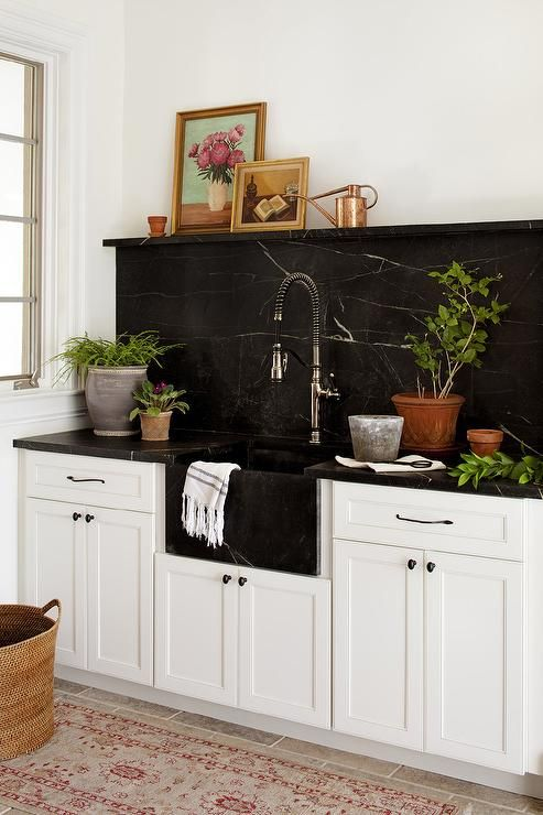 a farmhouse kitchen in white is spruced up and made more eye-catchy with a black marble backsplash and countertops