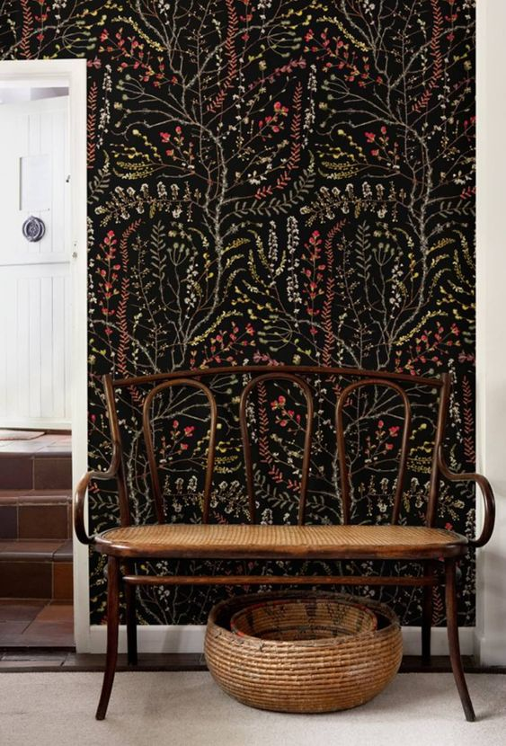 a cozy entryway with a catchy black botanical wallpaper wall that takes over the whole space