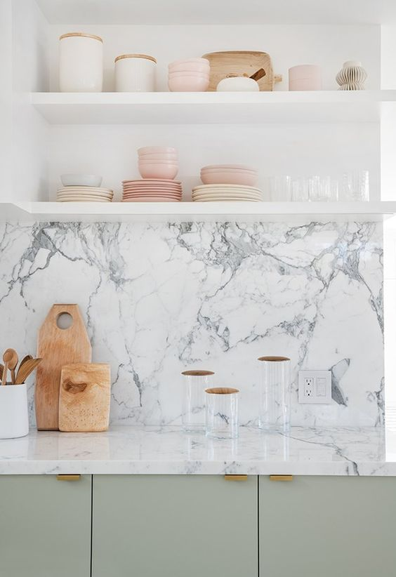 a light green kitchen with open shelving and a white marble backsplash and countertops is a chic space to be