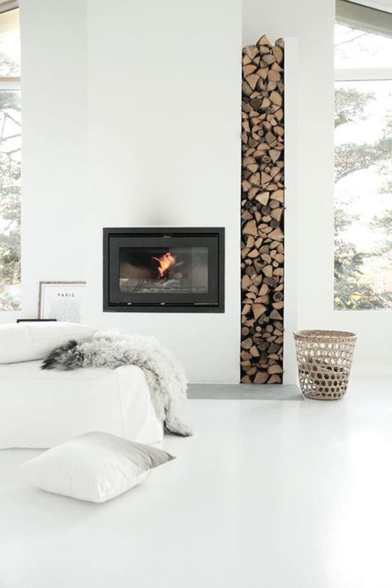 a minimalist all-white nook with a built-in fireplace and built-in firewood storage plus pillows looks heavenly and welcoming