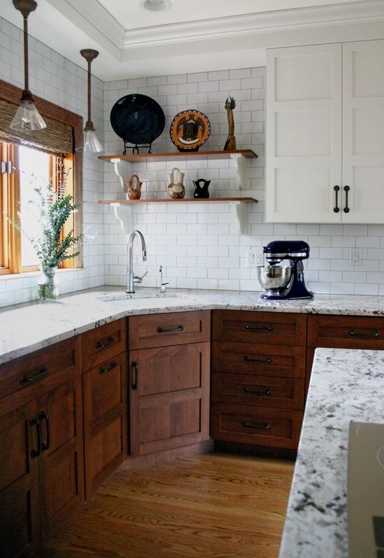 dark stained wood and white cabinets plus black metal handles and marble countertops for a rustic kitchen