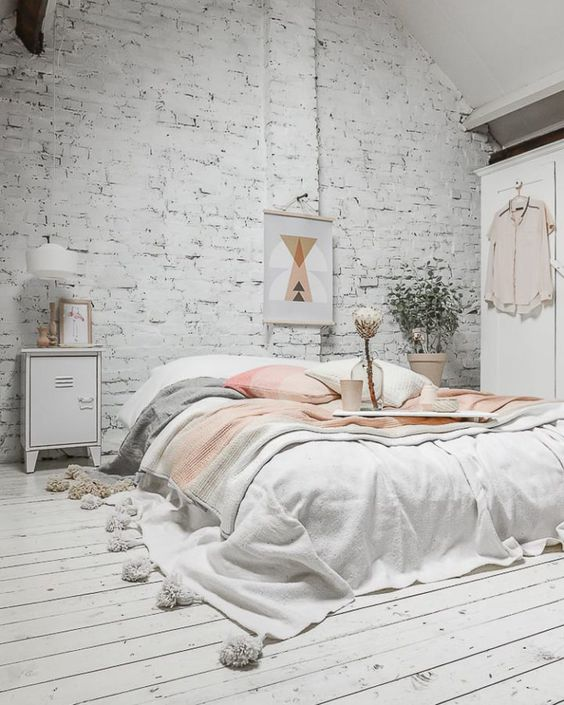 a beautiful and peaceful bedroom with a whitewashed brick wall and a plank floor for more interest