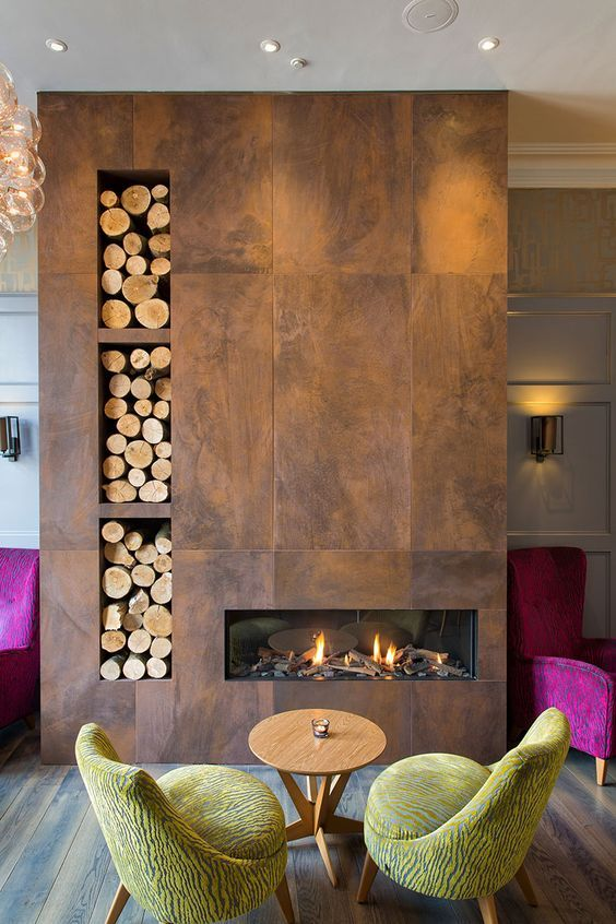 a bold room with a metal clad built-in fireplace and built-in firewood storage plus colorful furniture