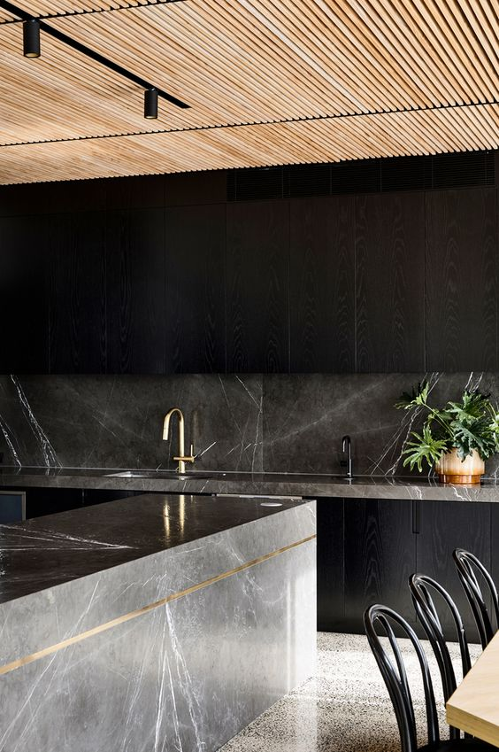 a minimalist black kitchen with sleek cabinets and a grey marble backsplash and countertops plus a kitchen island to make a statement