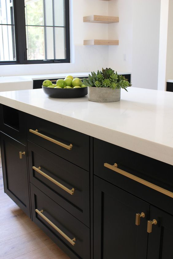 long brass handles stand out on black cabinets and make the kitchen look wow