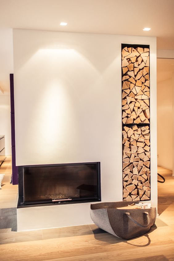 a minimalist built in fireplace with built in firewood storage next to it plus an additional felt bag with firewood