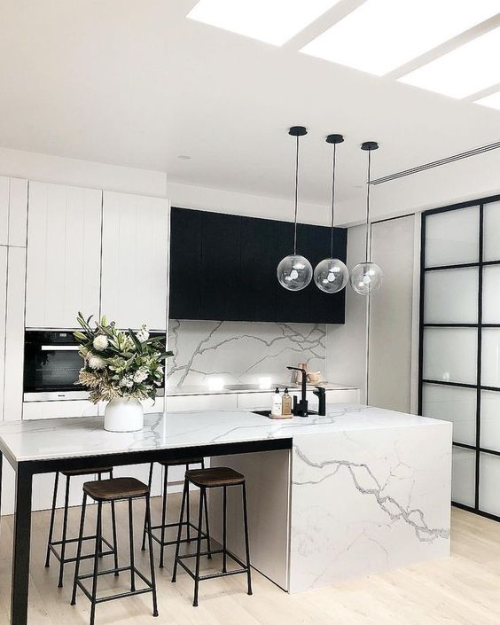 a minimalist contrasting kitchen with black and white cabinets, a white marble tile backsplash and kitchen island plus pendant lamps