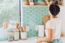 07 a neutral contemporary kitchen with a bright mint-colored backsplash done with hex tiles and wooden shelves plus touches of gold