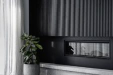 08 a dramatic black wooden slab wall with a built-in fireplace is a stylish idea for a minimalist space
