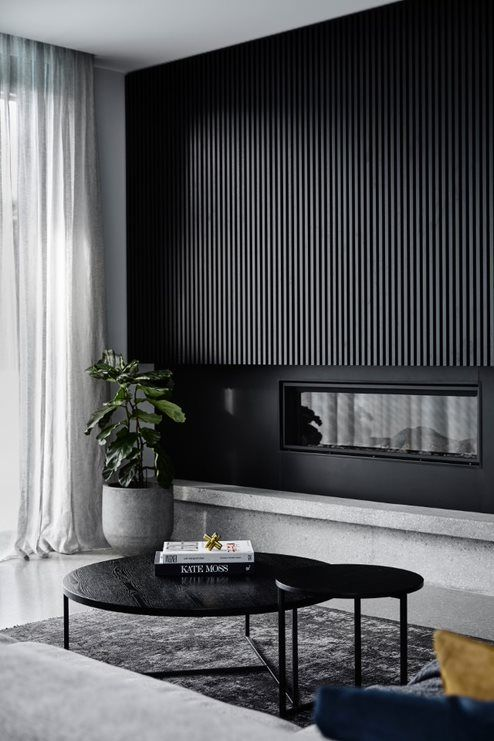 a dramatic black wooden slab wall with a built-in fireplace is a stylish idea for a minimalist space