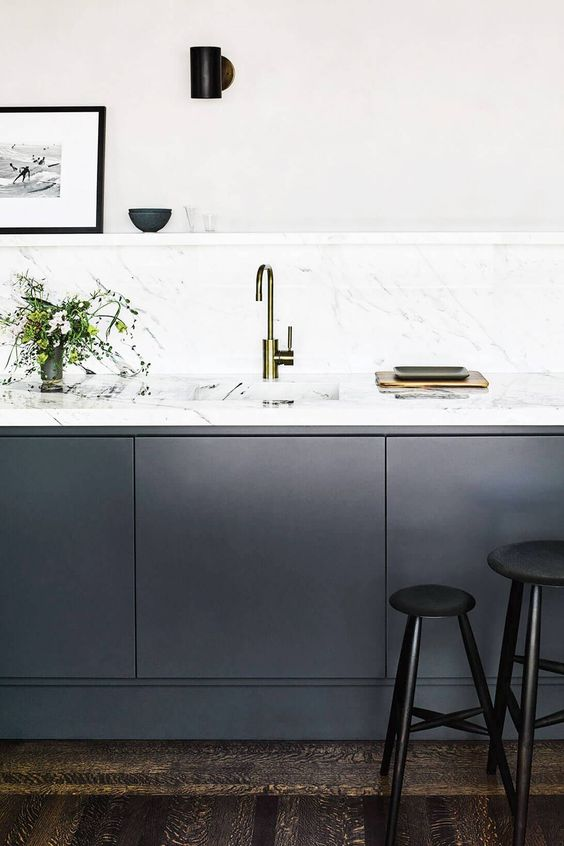 a minimalist kitchen with graphite grey cabinets and white marble countertops plus a backsplash looks really chic and wow