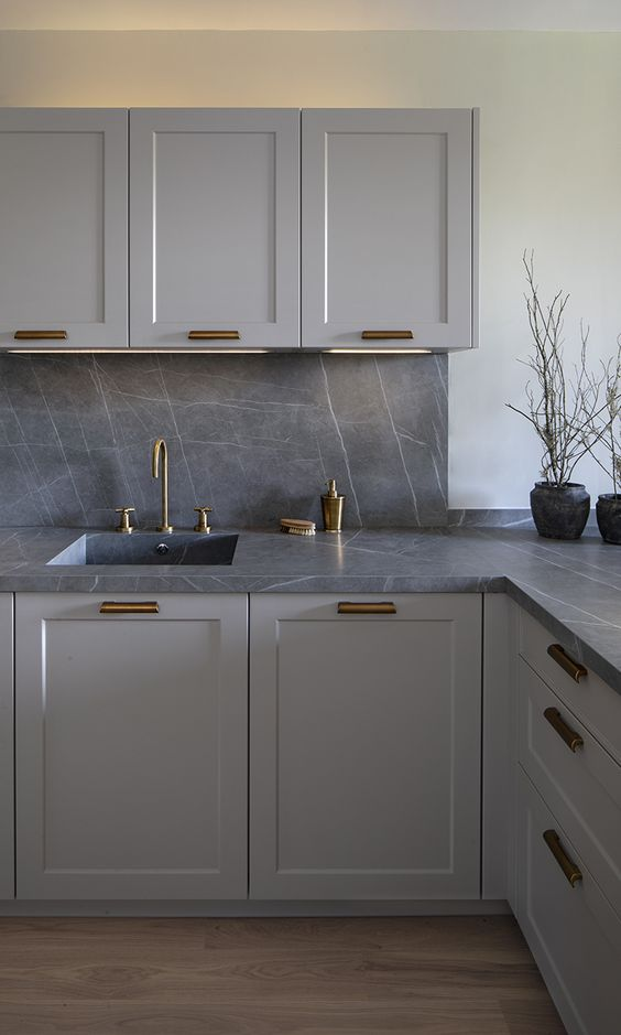 a minimalist light grey kitchen with chic grey marble countertops and a backsplash plus brass details for a refined feel