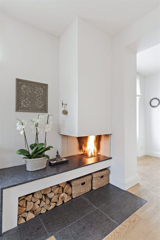 a modern ethanol fireplace and firewood storage built-in under it plus baskets for a slight rustic touch