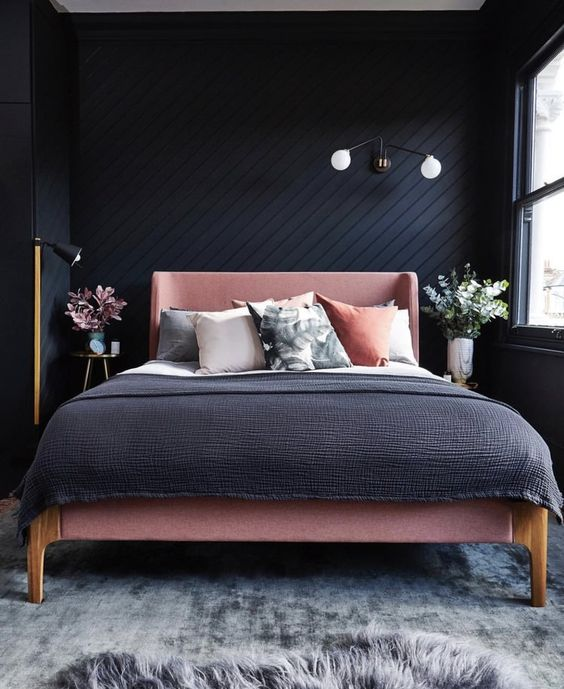 a moody bedroom with a black shiplap wall done in a geometric pattern and with moody decor around is refined