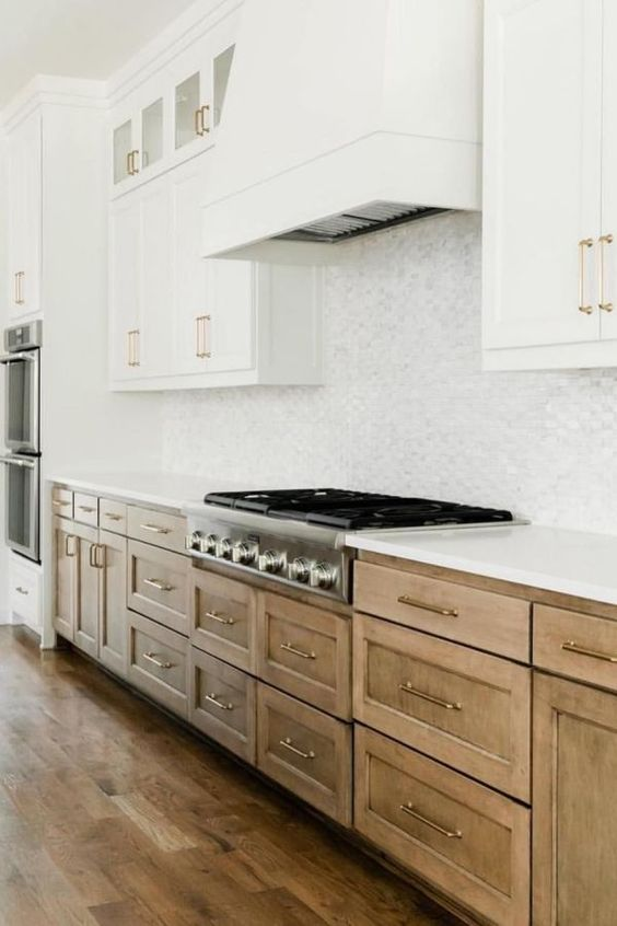 a stylish traditional kitchen with white upper cabinets, wooden lower ones, gold handles and a marble tile backsplash