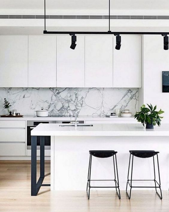 a minimalist monochromatic kitchen with sleek white cabinets, black stools and lamps and a gorgeous white marble backsplash