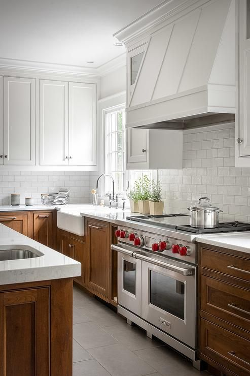 a modern farmhouse kitchen with white uppers and rich stained lower ones plus a white subway tile backsplash