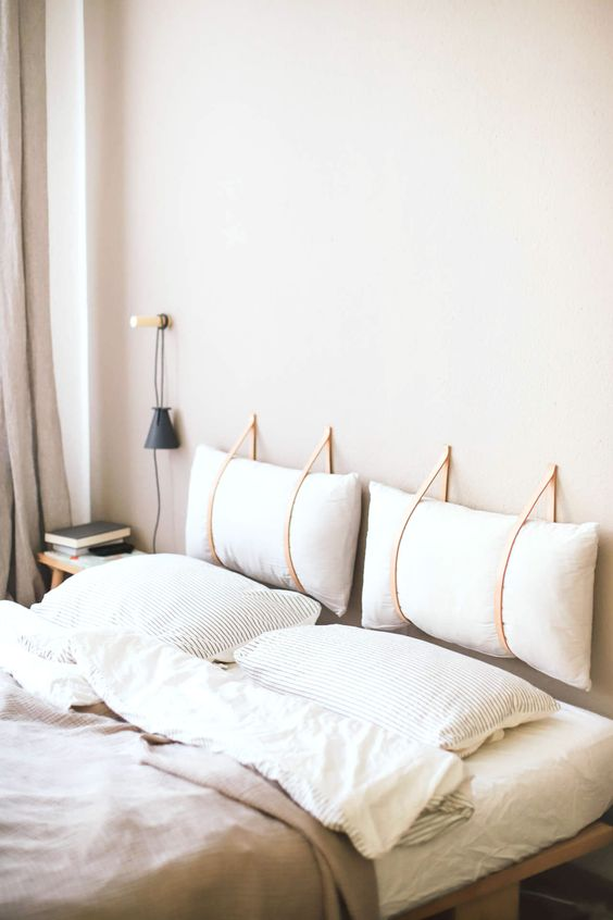 a neutral peaceful space with a headboard composed of two pillows hanging on leather