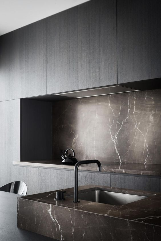 a minimalist sleek grey kitchen with a brown marble backsplash and countertops plus a matching sink for a wow effect