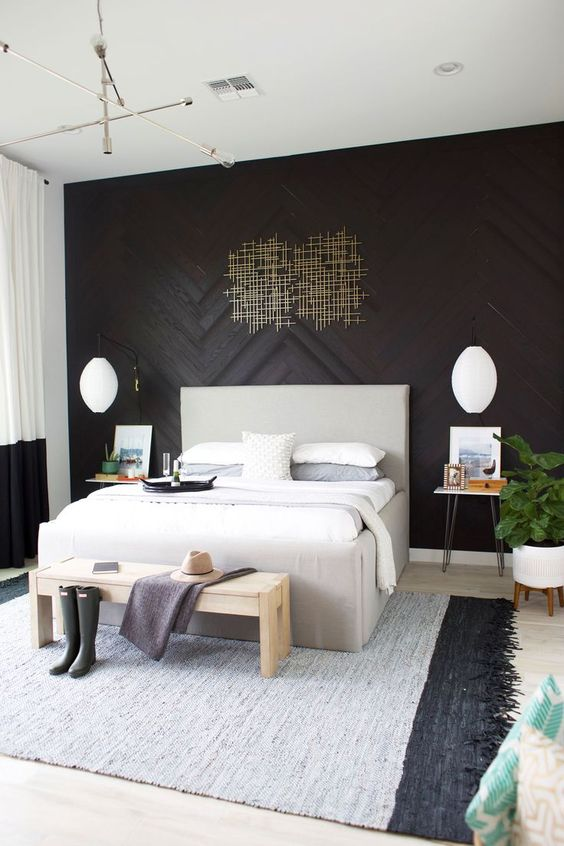 a refined black wood accent wall with an artwork, brass touches and black and white decor