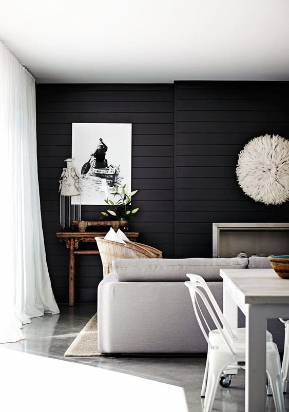 a Scandinavian living room with a black shiplap accent wall that makes a statement in this neutral space