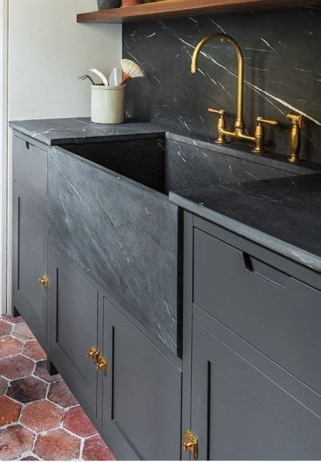 a moody graphite grey kitchen with a black marble backsplash and countertops, gold touches for more chic