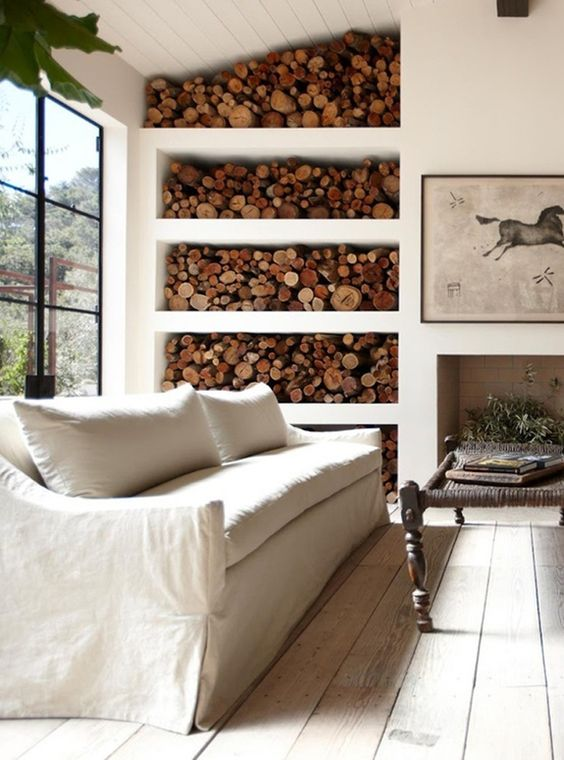 a non working fireplace with a larg eopen firewood storage space that becomes real part of decor here