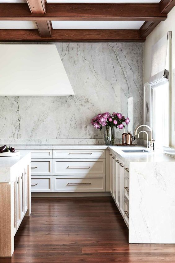 a refined glam kitchen done in neutrals, with a large hood, wooden beams and a white marble backsplash and countertops