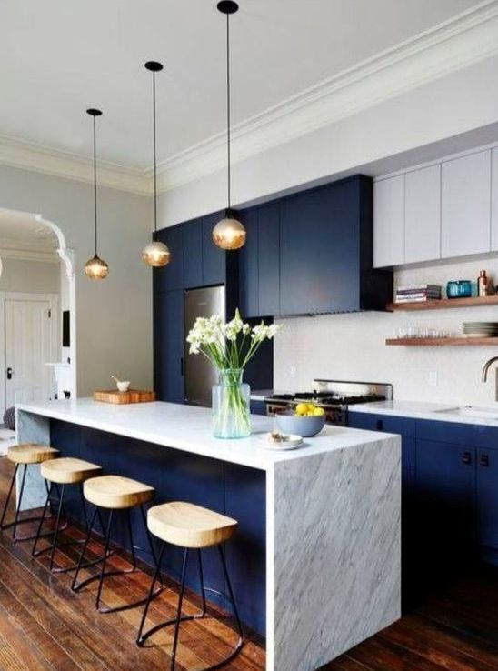 bold blue and white cabinets plus a marble kitchen island look modern and luxurious