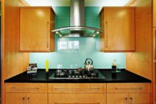 13 oversized turquoise tiles on the backsplash stand out in a warm-colored kitchen and give it a character