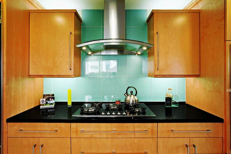oversized turquoise tiles on the backsplash stand out in a warm colored kitchen and give it a character