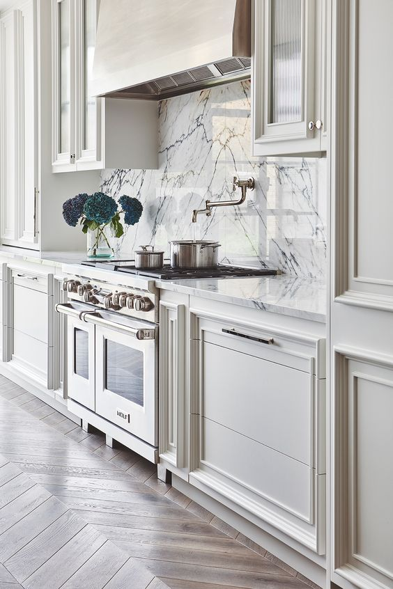 a stylish farmhouse vintage kitchen in neutral shades, with a white marble backsplash and a vintage hood and cooker