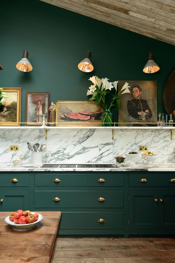 a stylish vintage-inspired emerald kitchen with a white marble backsplash and countertops plus gold touches