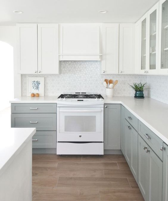 a beautiful kitchen with dove grey and white cabinets plus a mosaic tile backsplash