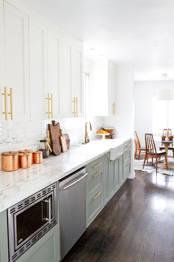 a trendy two-tone kitchen in white and light green, with gold touches and a white marble backsplash and countertops