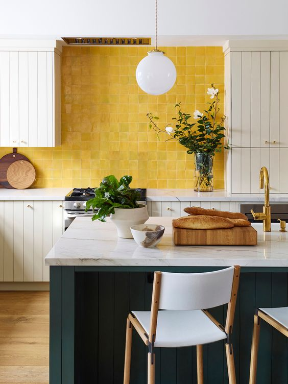 a vintage-inspired kitchen with white cabinets, a black kitchen island, white stone countertops and sunny yellow tiles on the backsplash