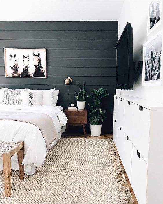 a statement wall done with black shiplap is a chic idea for a boho or rustic bedroom, and the texture is cool
