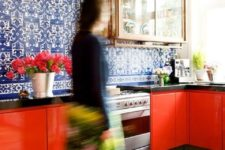 17 a whimsical kitchen with red cabinets, black countertops and bold blue and white tiles covering the whole wall