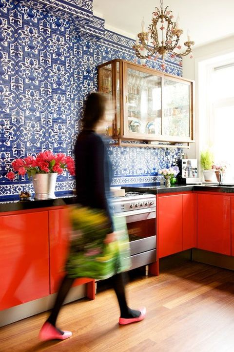 a whimsical kitchen with red cabinets, black countertops and bold blue and white tiles covering the whole wall